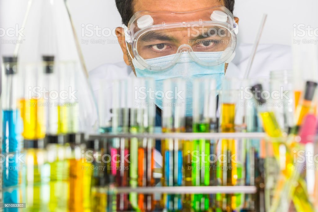 Man scientist looking at colorful chemical solution in many test...