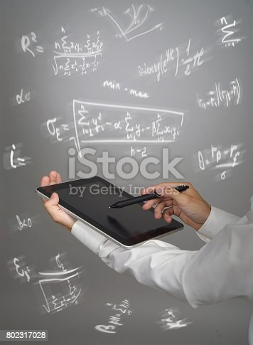 istock Man scientist or student holding tablet PC and working with various high school maths and science formulas 802317028
