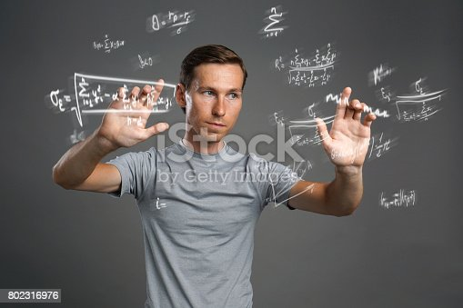 649719220istockphoto Man scientist or student working with various high school maths and science formulas 802316976