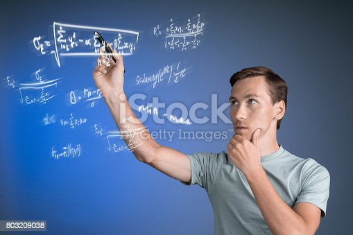 istock Man scientist or student working with various high school maths and science formulas 803209038