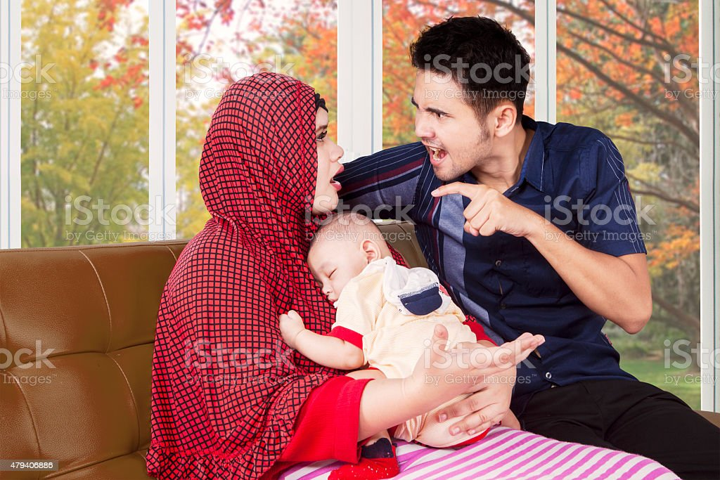 Man scolding his wife while holding baby stock photo