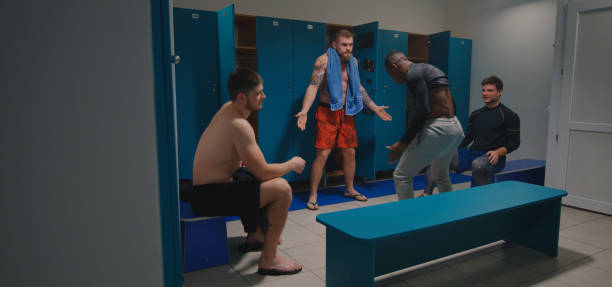 Man scolds team members Full shot of man scolds team mates for poor performance in locker room black men locker room stock pictures, royalty-free photos & images