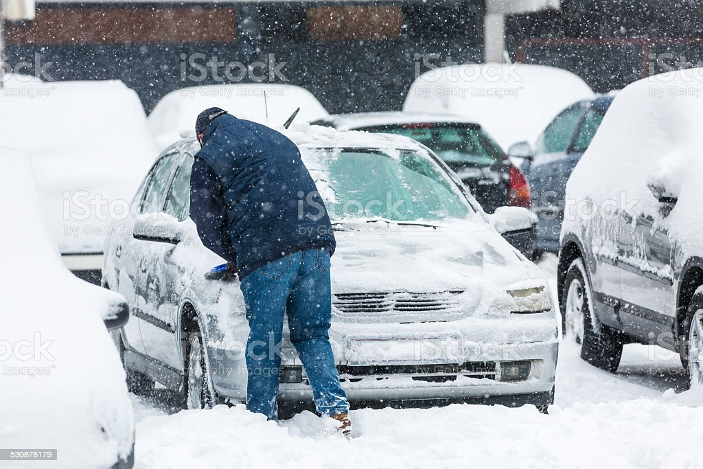 Man scraping frozen snow from car windows stock photo
