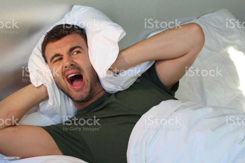 Man screaming at home while covering ears stock photo
