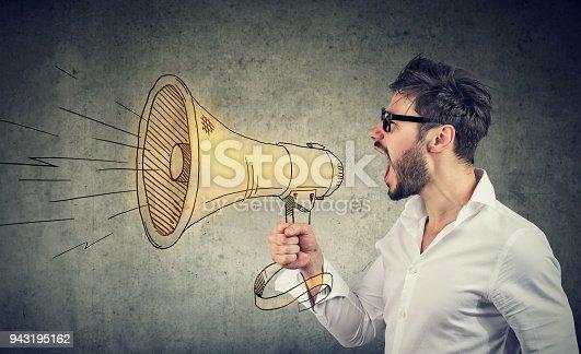 910149000istockphoto Man screaming into loudspeaker 943195162