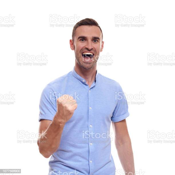 man screaming mouth open, hold head hand, wear casual blue shirt, isolated white background, concept face emotion.