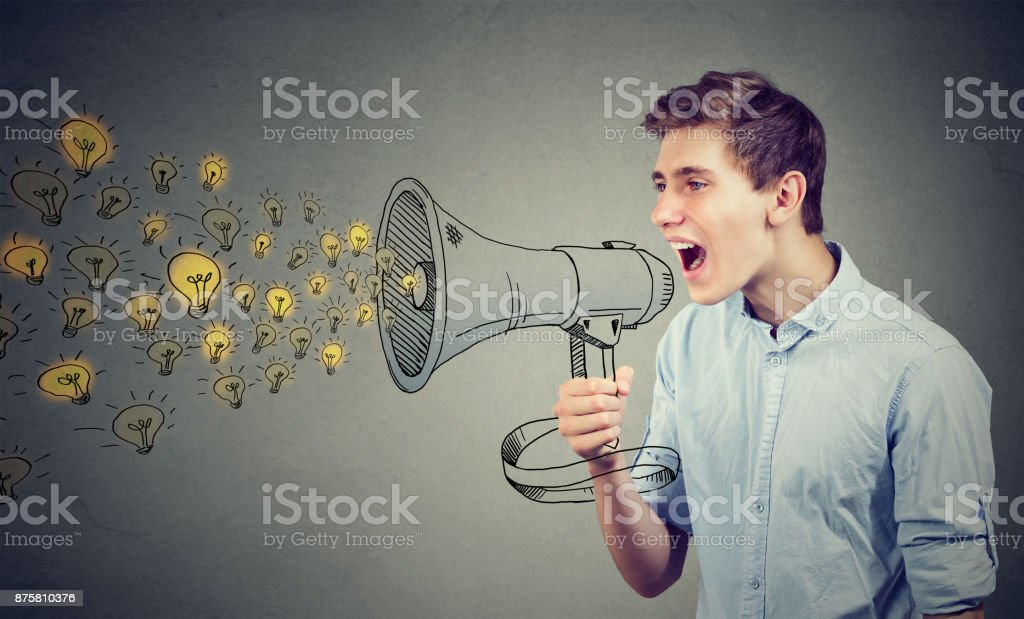 Man screaming out his ideas loud in megaphone isolated on gray wall background stock photo
