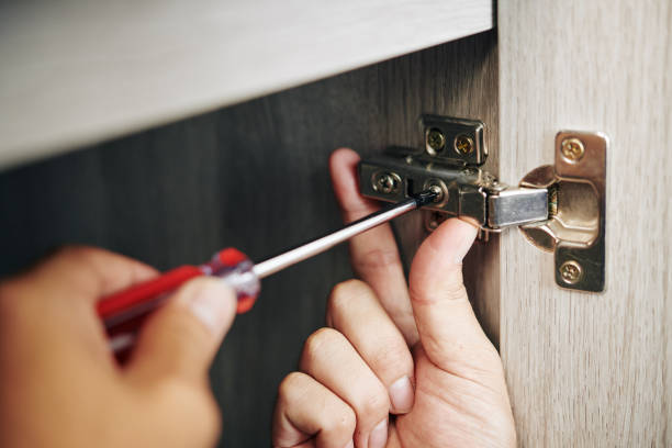 Man screwing door hinge stock photo