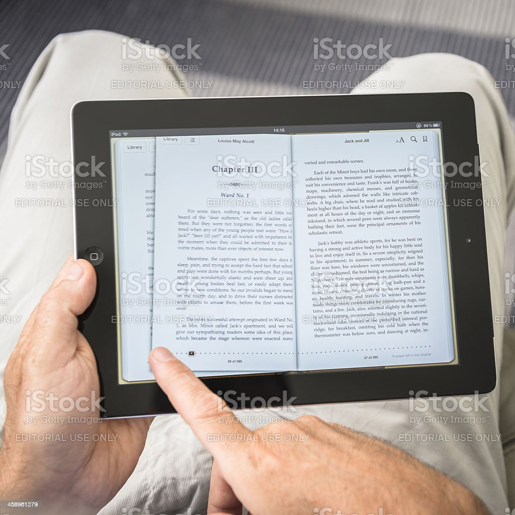 Man scrolling the pages of an ebook with Ipad royalty-free stock photo