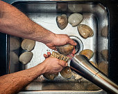 Man scrubbing clams in a kitchen sink under running water in preparation for cooking them.