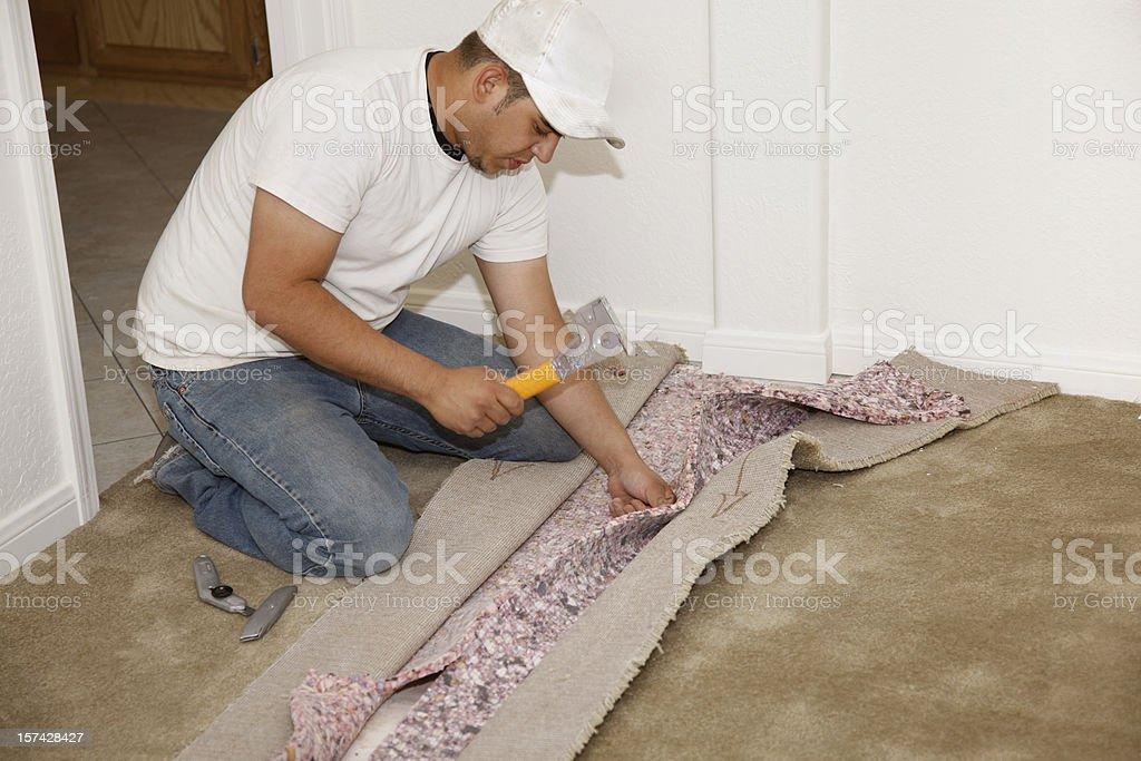 Man Seaming New Carpet Installation stock photo