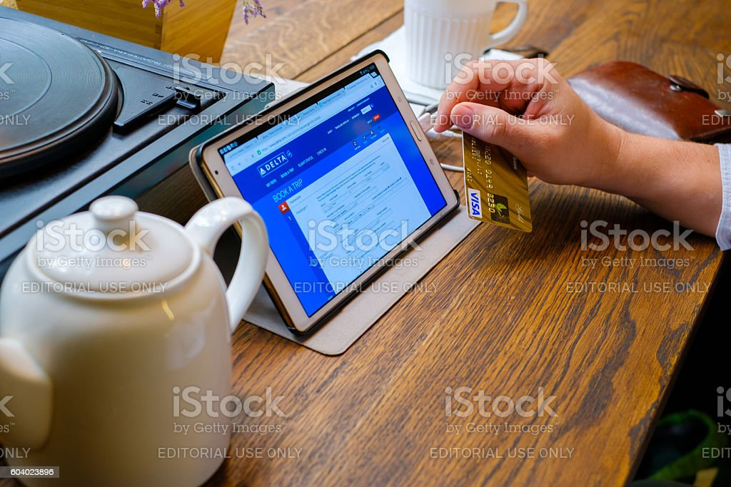Man searching for a trip on popular travel booking site stock photo