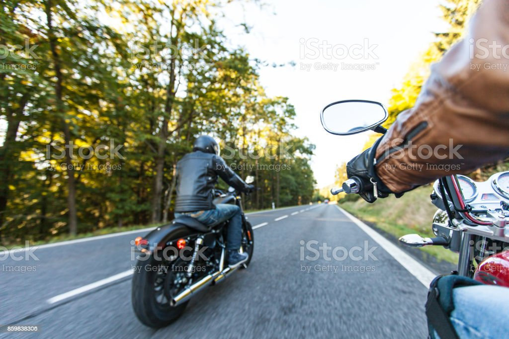 Man seat on the motorcycle on the forest road стоковое фото