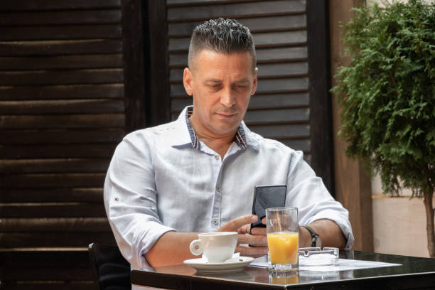 A man seated in a restaurant deliberately looks into the phone and drinks his drink stock photo
