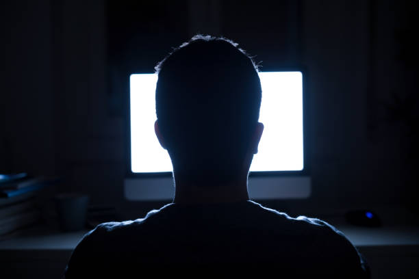 Man seated in front of computer monitor at night Silhouette of man's head in front of computer monitor light at night computer crime stock pictures, royalty-free photos & images