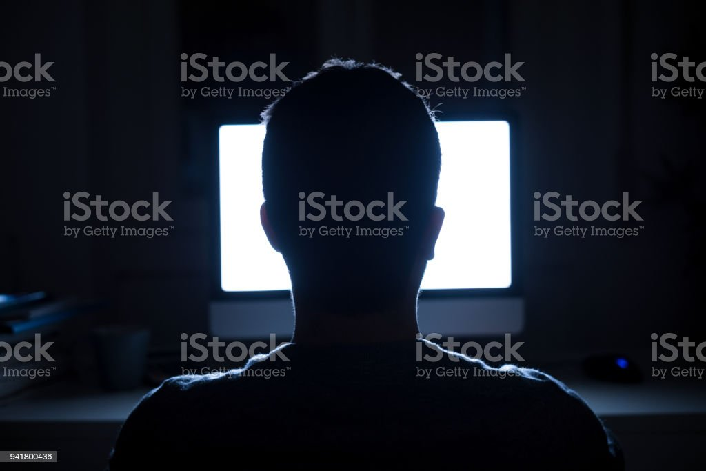 Man seated in front of computer monitor at night stock photo