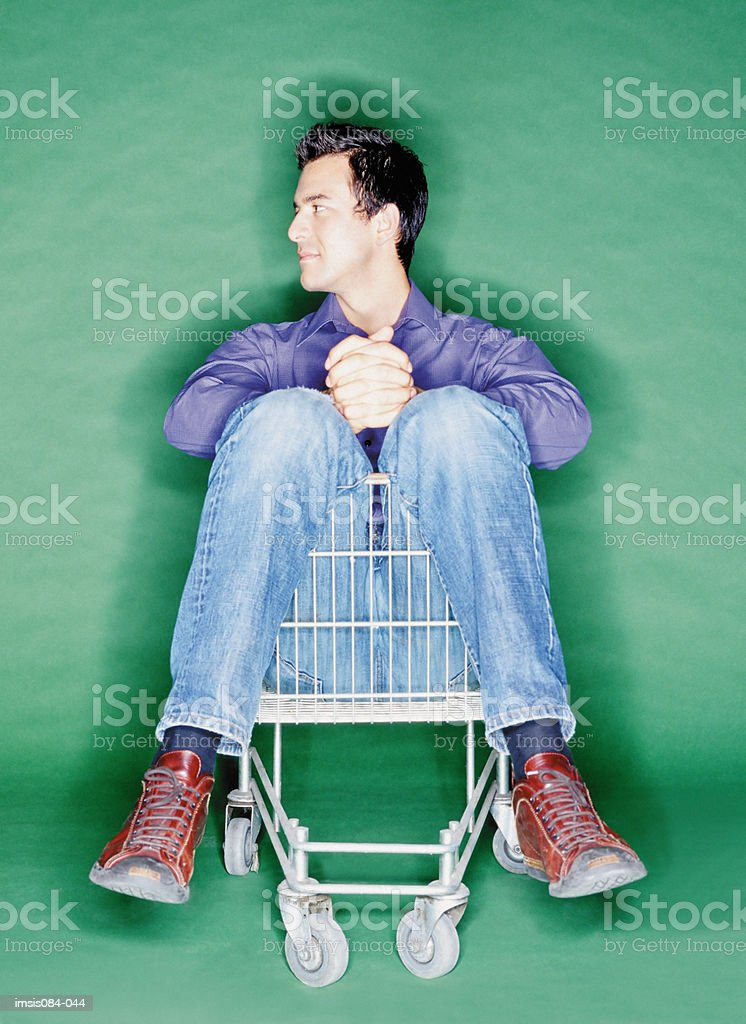 Man seated in shopping trolley royalty-free stock photo