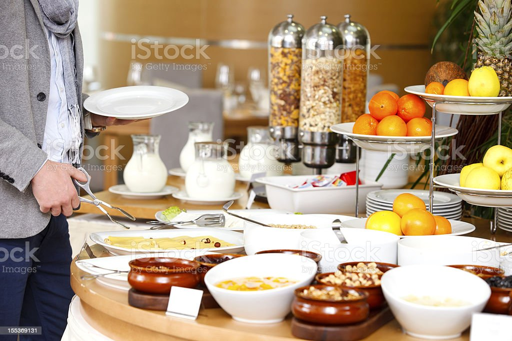 Man selecting his meal from a breakfast buffet stock photo