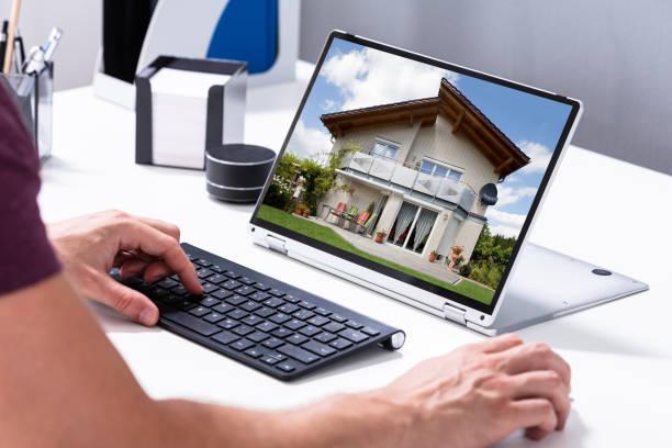 Mann wählt neues Haus auf Laptop zu Hause – Foto