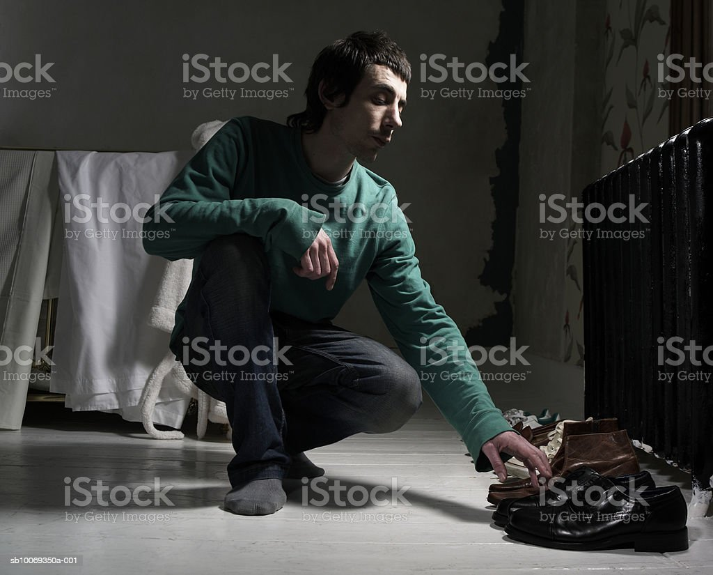 Man selecting shoes in home royalty-free stock photo
