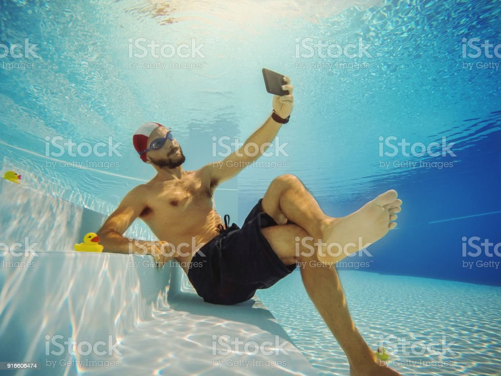 Man selfie underwater with mobile phone stock photo
