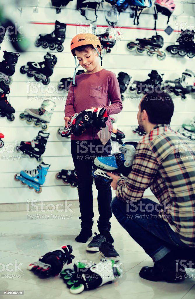 Garoto de assistir homem vendedor na tentativa patins - foto de acervo