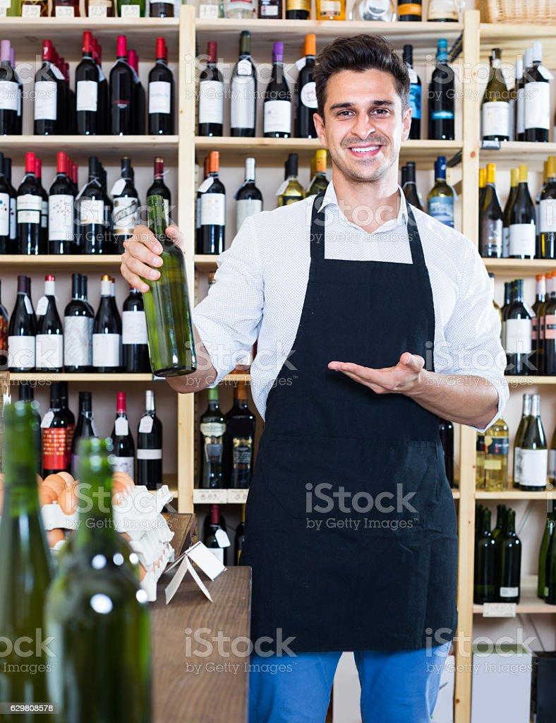 man seller holding bottle of wine in shop stock photo
