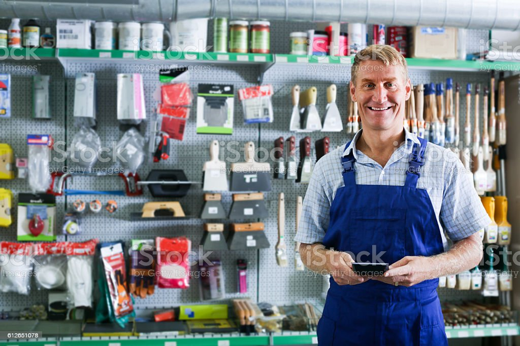 man seller standing in supermarket stock photo