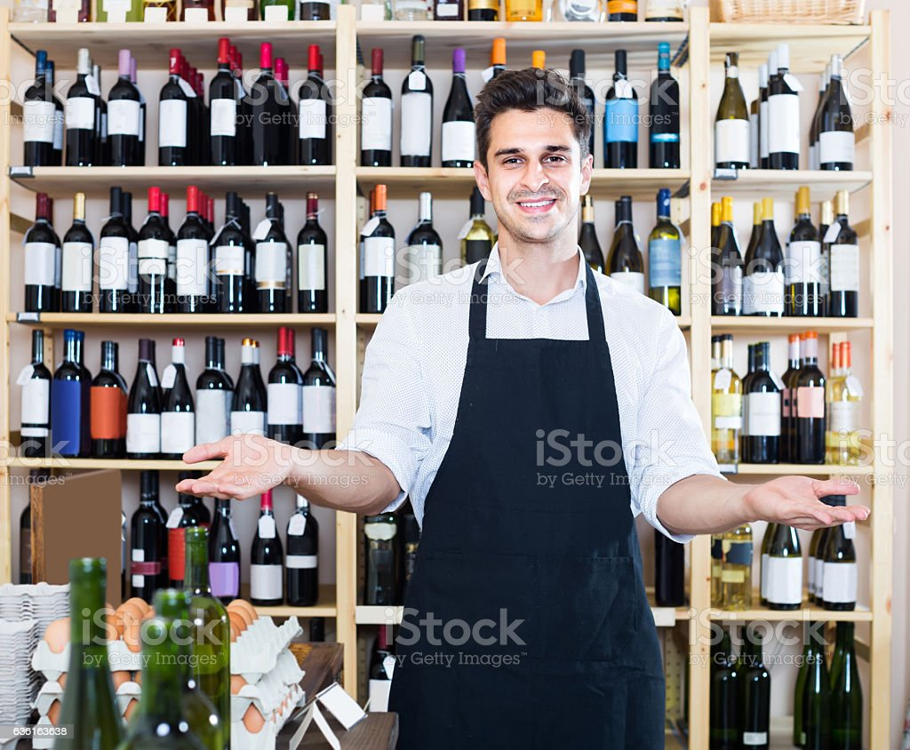 man seller wearing uniform standing in shop with wine stock photo
