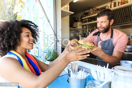 istock Man selling burgers and sandwiches in food truck 1170228804