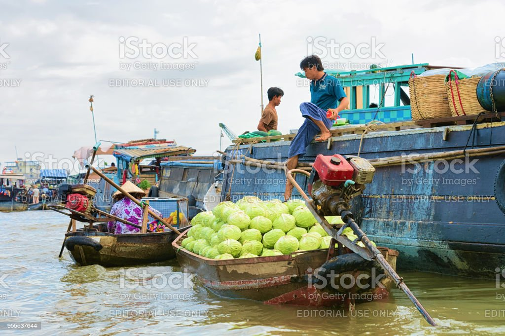 Man selling cabbage from the boat at the Floating market at the delta...