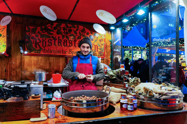 Man selling chestnuts at Christmas Market at Gendarmenmarkt Winter Berlin Berlin, Germany - December 8, 2017: Man selling chestnuts at Christmas Market at Gendarmenmarkt in Winter Berlin, Germany. Advent Fair Decoration and Stalls with Crafts Items on the Bazaar. gendarmenmarkt stock pictures, royalty-free photos & images