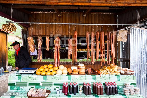 Transfagarasan, Romania - 6 July, 2016: a man sells a selection of cured meats and salami, as well as a range of locally produced cheeses, on his market stall high up on the famous Transfagarasan road in the Transylvania region of Romania. The man is looking at the camera, while the meat he sells is attractively hung up and displayed in a row. Horizontal colour image with copy space.