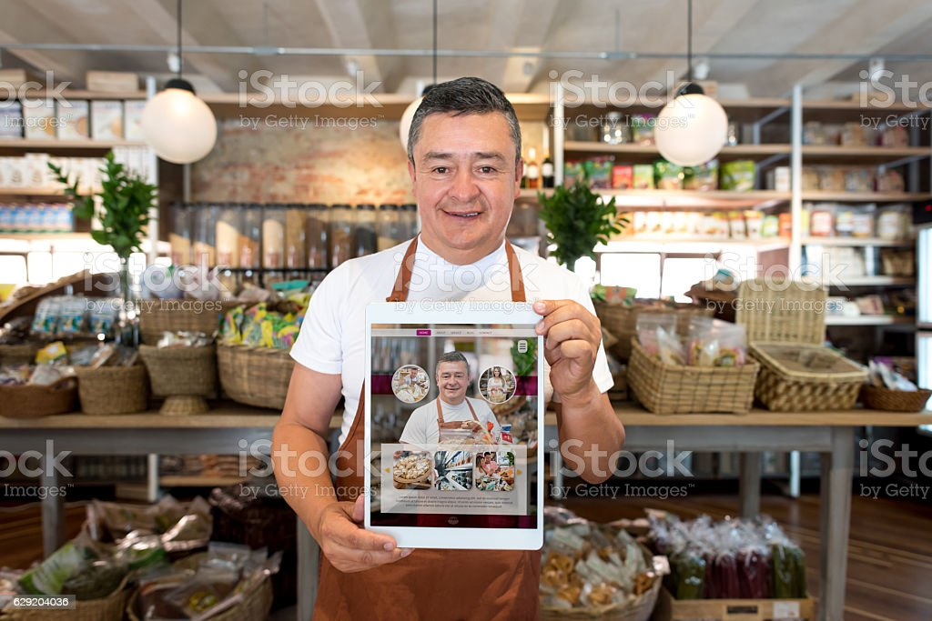 Man selling food online at a grocery store stock photo