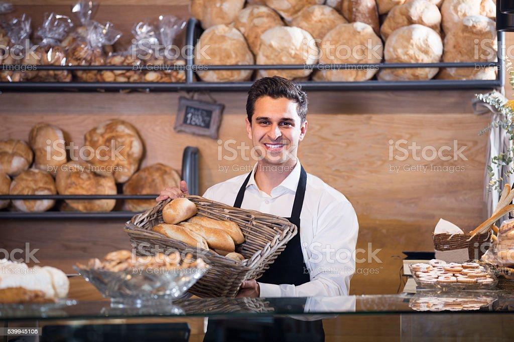 Man selling fresh pastry and baguettes stock photo