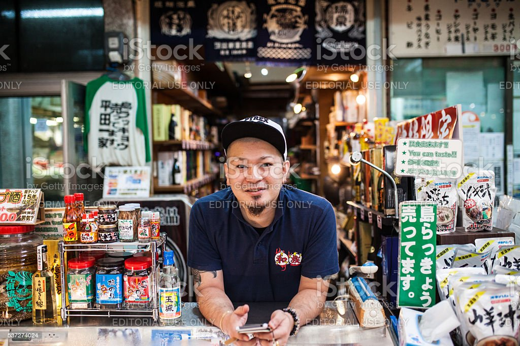 Man selling general goods in Okinawa's Makeshi market. Naha, Japan - August 11, 2015: The people of Okinawa's Makeshi market. Horizontal Stock Photo