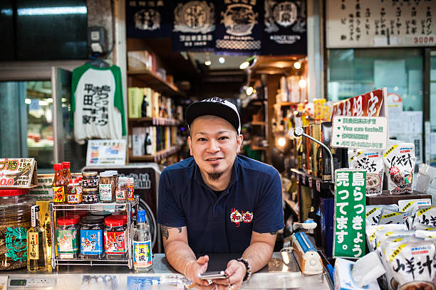 Man selling general goods in Okinawa's Makeshi market. Naha, Japan - August 11, 2015: The people of Okinawa's Makeshi market. naha stock pictures, royalty-free photos & images