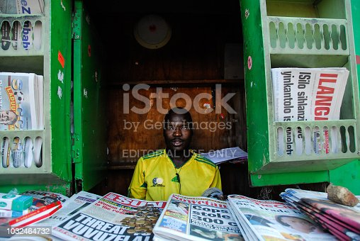Johannesburg , Gauteng / South Africa -august 31 2012 : man sitting in a kiosk selling newspapers afternoon Johannesburg City CBD