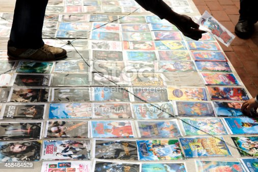Sabadell, Spain - April 3, 2011:Man selling pirated dvds in the street. The dvds, displayed on the floor and wrapped in plastic, sell for two or three euros, and mostly are recent movie titles. Althought illegal, sometimes this activity is tolerated in Spain.