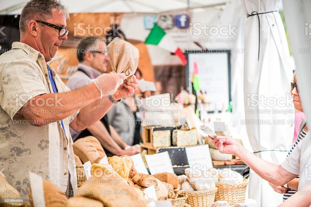 man sells artisan bread on food festival stock photo