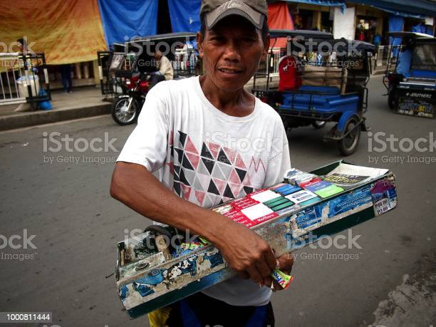 Man sells cigarettes candies and snack items along a street in city picture id1000811444?b=1&k=6&m=1000811444&s=612x612&h=elu1xwf5sscdf ym6hlroc7tluzrnkgfvuytmbe2fie=