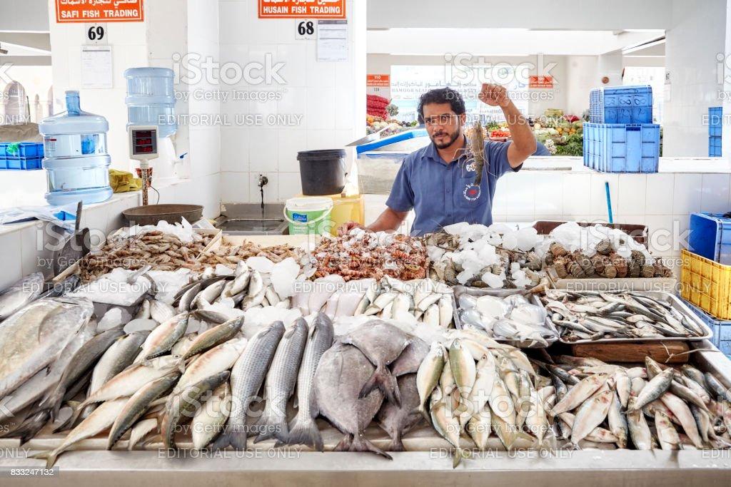 Man sells seafood at the local fish market. stock photo