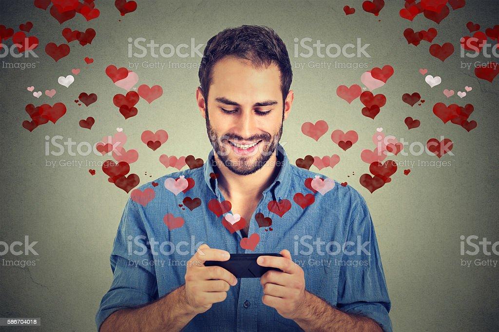 man sending love sms message on mobile phone foto de stock libre de derechos