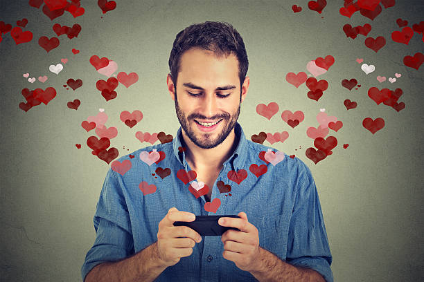 man sending love sms message on mobile phone - romantische aktivität stock-fotos und bilder