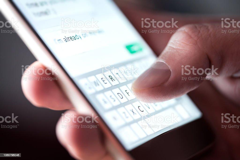 Hombre enviar mensaje de texto y sms con smartphone. Mensajes de texto de chico y con teléfono móvil por la noche en la oscuridad. Concepto de comunicación o de sexting. Dedo escribiendo con el teclado del teléfono móvil. - foto de stock