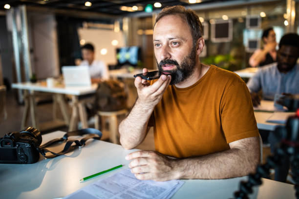 Man sending voice message on smart phone from the office Bearded mature  man   sitting in the office, using smart phone   for sending voice message speech recognition stock pictures, royalty-free photos & images