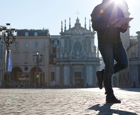Man sends text message while walking through piazza, Turin, Piedmont, Italy