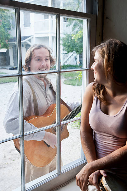 Man serenading woman through window Man with guitar serenades young woman.  Main focus on man serenading stock pictures, royalty-free photos & images