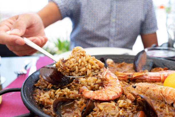 man serving a typical spanish seafood paella - paella stock photos and pictures