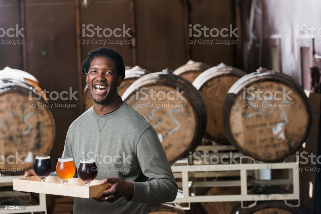 Man serving beer at microbrewery stock photo